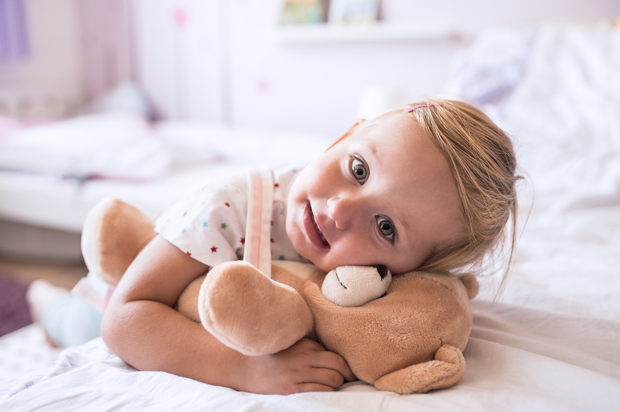 graphicstock cute little girl with her teddy bear at home lying on bed in bedroom SOx0Tk5Hz