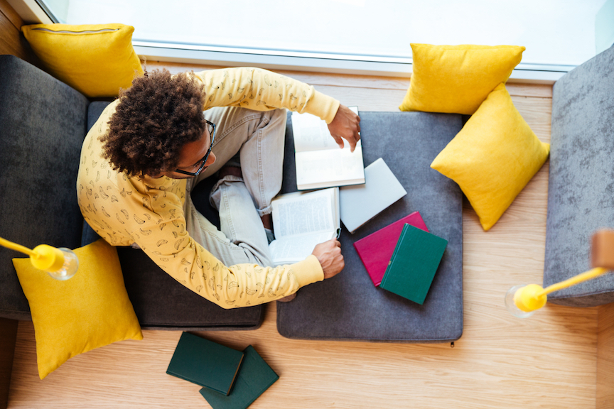 graphicstock top view of african young man studying and reading books at home S bqhiB83e